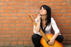 Woman with a cigarette and a guitar Royalty Free Stock Photography