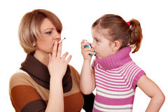 Woman with cigarette and little girl with inhaler Stock Photos
