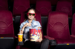 Woman at the cinema. Young woman sitting alone in the cinema and watching a movie Stock Images