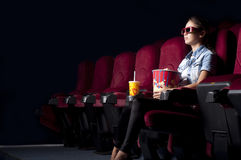 Woman at the cinema. Young woman sitting alone in the cinema and watching a movie Royalty Free Stock Photo