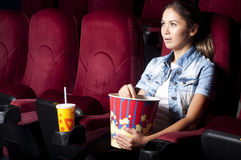 Woman at the cinema. Young woman sitting alone in the cinema and watching a movie Royalty Free Stock Photos
