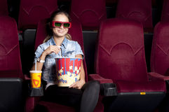 Woman at the cinema eat popcorn. Young woman sitting alone in the cinema and watching a movie Royalty Free Stock Image
