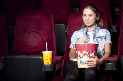 Woman at the cinema eat popcorn. Young woman sitting alone in the cinema and watching a movie Royalty Free Stock Images