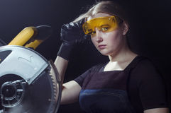 Woman with a circular disk saw Stock Images