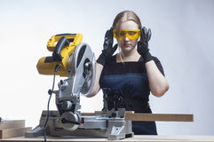 Woman with a circular disk saw Stock Image