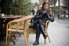 Woman in the city. Young attractive is sitting in a street cafe and using her cell phone Stock Image