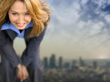 Woman and City. Young business woman smiling with city and clouds far in the distance behind her Stock Photos