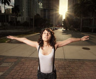 Woman in the city. Young stylish woman standing with arms extended in the city with the sunset in the background Stock Image