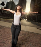 Woman in the city. Young stylish woman standing with arms extended in the city with the sunset in the background Stock Photography