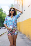 Woman in the city on the background of a yellow wall, holding milkshake, fresh juice in glasses, wearing shirt with the Stock Images
