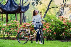 A woman with city bicycle near traditional chinese pavilion in a park. Portrait of attractive female with city bicycle near traditional chinese pavilion in a Stock Photography
