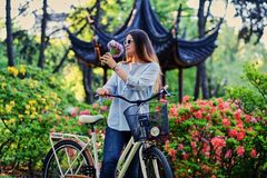 A woman with city bicycle near traditional chinese pavilion in a park. Portrait of attractive female with city bicycle near traditional chinese pavilion in a Royalty Free Stock Photo