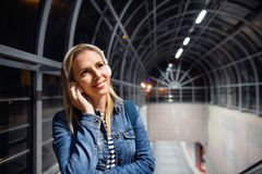 Woman in the city at night earphones on her ears, listening musi Royalty Free Stock Photography