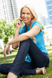 Woman in city park talking on phone Stock Photo