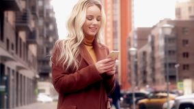 Stylish woman in city. Smiling and using smartphone. stock footage