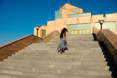 Woman on a city street climbs the stairs Royalty Free Stock Images