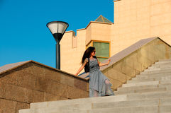 Woman on a city street climbs the stairs Stock Images