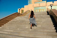 Woman on a city street climbs the stairs Stock Photos