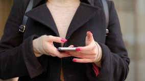 Woman on a city street using a mobile phone. Happy excited young woman receiving discount for shopping while checking email box on mobile calling for sharing stock video
