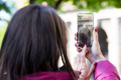 Woman in a city taking photographs with transparent phone. Woman is a tourist taking photographs in an European city with her ultra modern transparent smartphone stock photos