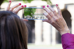 Woman in a city taking photographs with transparent phone. Woman is a tourist taking photographs in an European city with her ultra modern transparent smartphone royalty free stock image