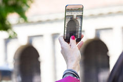 Woman in a city taking photographs with transparent phone Stock Photography