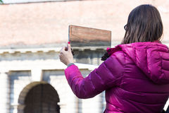 Woman in a city taking photographs with transparent phone. Woman is a tourist taking photographs in an European city with her ultra modern transparent smartphone royalty free stock photos