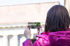 Woman in a city taking photographs with transparent phone. Woman is a tourist taking photographs in an European city with her ultra modern transparent smartphone royalty free stock photo