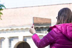 Woman in a city taking photographs with transparent tablet. Woman is a tourist taking photographs in an European city with her ultra modern transparent tablet royalty free stock image