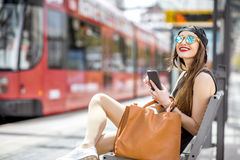 Woman at the city transport stop. Lifestyle portrait of a stylish woman in black dress and hat sitting with phone on the modern tram stop Royalty Free Stock Image