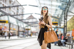 Woman at the city transport stop. Lifestyle portrait of a stylish woman in black dress and hat standing with bag and phone on the tram stop in the modern city Stock Images