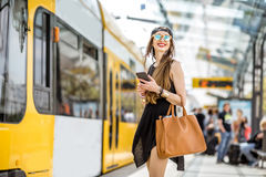 Woman at the city transport stop. Lifestyle portrait of a stylish woman in black dress and hat standing with bag and phone on the tram stop in the modern city Royalty Free Stock Images