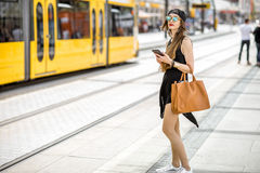 Woman at the city transport stop. Lifestyle portrait of a stylish woman in black dress and hat standing with bag and phone on the tram stop in the modern city Royalty Free Stock Photos