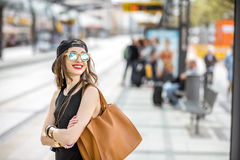 Woman at the city transport stop. Lifestyle portrait of a stylish woman in black dress and hat standing with bag on the tram stop in the modern city Stock Image