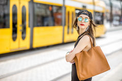 Woman at the city transport stop. Lifestyle portrait of a stylish woman in black dress and hat standing with bag on the tram stop in the modern city Stock Images