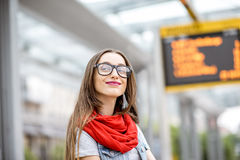 Woman at the city transport stop. Portrait of a young woman waiting for the public transport standing on the tram stop with timetable on the background Stock Photos