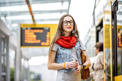Woman at the city transport stop. Portrait of a young woman waiting for the public transport standing on the tram stop with timetable on the background Stock Images