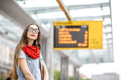 Woman at the city transport stop. Sad woman waiting for the public transport standing on the tram stop with timetable on the background Stock Image