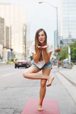 Woman on city urban street doing yoga Stock Photos