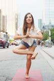 Woman on city urban street doing yoga Stock Image
