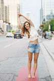 Woman on city urban street doing yoga Stock Images