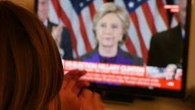 Woman clapping hands watching TV after US elections listening to Hillary Clinton speech stock footage