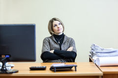 Woman with clasped hands dreaming at working place Stock Photos
