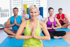 Woman with class meditating in fitness studio Stock Photos