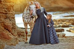 Woman with daughter and mottled horse royalty free stock photos