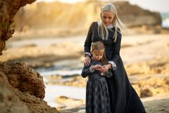 Woman and bonding with little daughter in classic dress standing on the coast stock photography