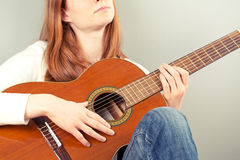 Woman with a classical guitar making music Stock Photos