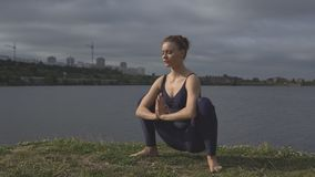Woman in classical yoga pose, energy concentration. Beautiful woman in classical yoga pose, energy concentration, cloudy sky and lake on background. sport, yogi stock footage