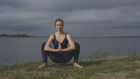 Woman in classical yoga pose, energy concentration. Cloudy sky and lake on background. sport, yogi, meditation and healthy lifestyle concept stock footage