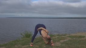Woman in classical yoga pose, energy concentration. Woman in classical Yogi pose, energy concentration, cloudy sky and lake on background. sport, yoga stock footage